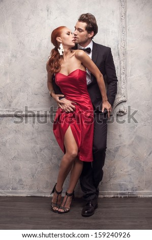 Beautiful couple in classical outfits. Standing and kissing with passion  - stock photo