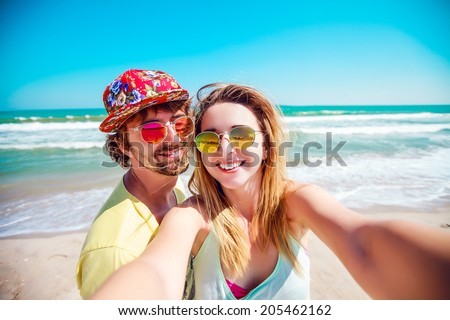 Beautiful couple in love doing self on a tropical beach, enjoy the holidays, sunbathe and have fun. - stock photo