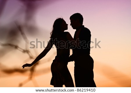 Beautiful couple in love in kontrazhur at sunset. Silhouette guys and girls at sunset. They dance.