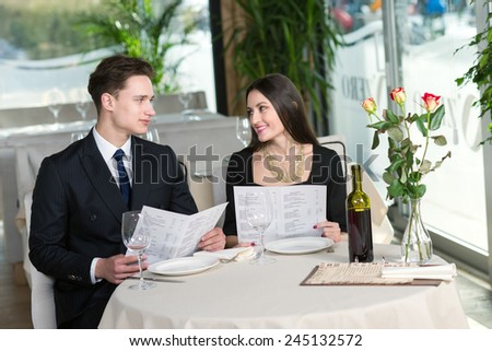 Beautiful couple in love is having romantic dinner together. Both are reading menus and looking at each other - stock photo