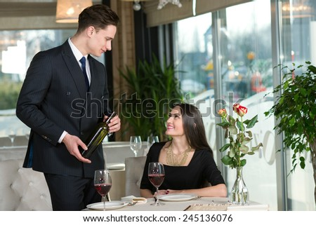 Beautiful couple in love is having romantic dinner together. Handsome man is proposing wine to his beautiful wife - stock photo