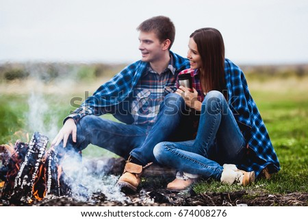 Beautiful couple in love sitting near a fire in a plaid in the field