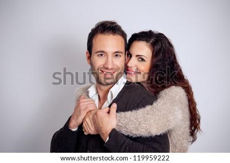 Beautiful couple in studio on gray background - stock photo