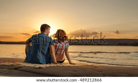 Beautiful couple is sitting on the beach and looking at each other