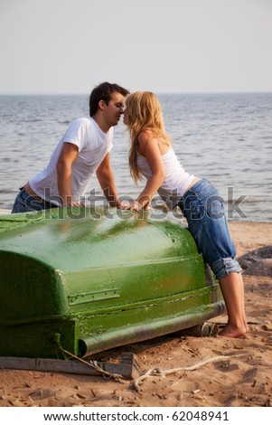 beautiful couple kissing on a beach near old boat - stock photo