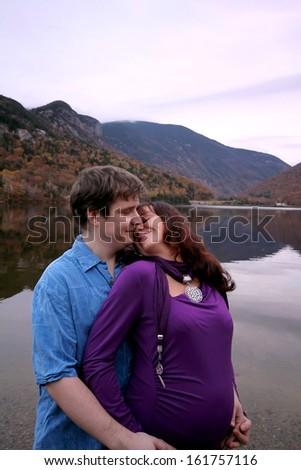 Beautiful couple kissing on the sunset near the lake.  - stock photo