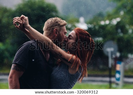 beautiful couple kissing outside in the rain - stock photo