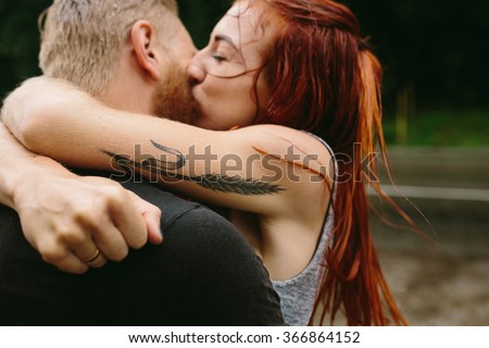 beautiful couple kissing outside in the rain - stock photo