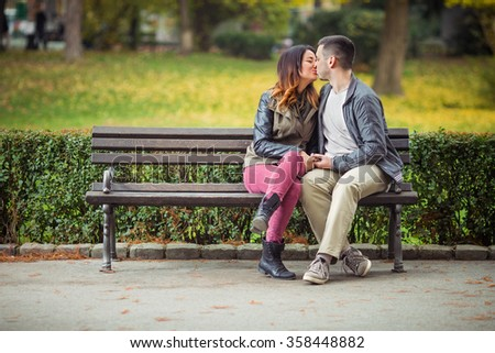 Beautiful couple kissing while sitting on a park bench - stock photo