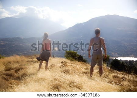 beautiful couple looking at beautiful valley - stock photo