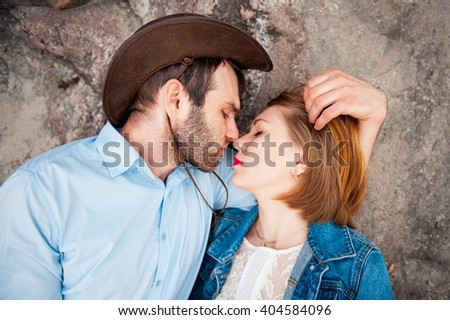 beautiful couple lying and hugging each other near a mountain river. guy in a cowboy hat and a girl in a dress and denim jacket - stock photo
