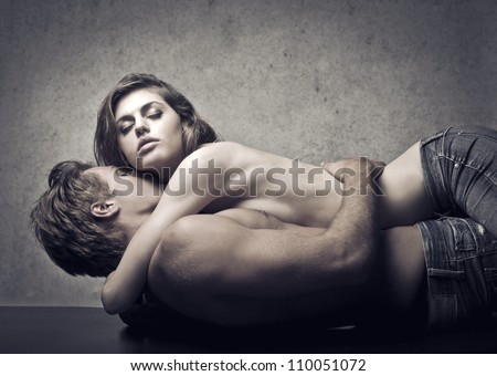 Beautiful couple lying on a table and hugging - stock photo