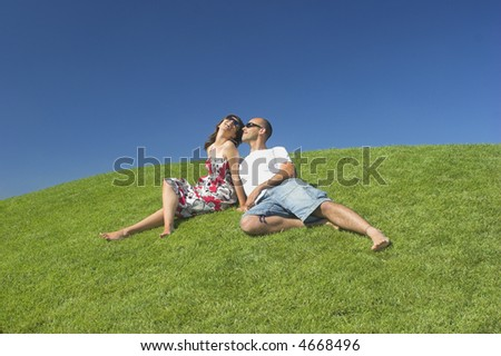 Beautiful couple of boyfriends relaxing on a beautiful green field - stock photo