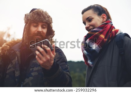 Beautiful couple of hikers laughing while looking to the mobile screen, young couple of backpackers enjoying a day out in nature during hike, travelers using mobile navigation in mountains - stock photo