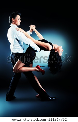 Beautiful couple of professional artists dancing passionate dance. - stock photo