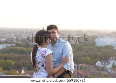 Beautiful couple on a  on a rooftop with an amazing view of the city behind
