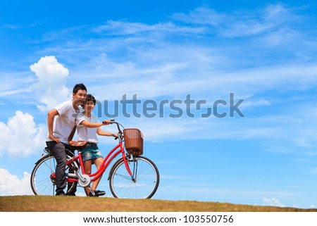 Beautiful Couple on bicycle with nice blue sky - stock photo