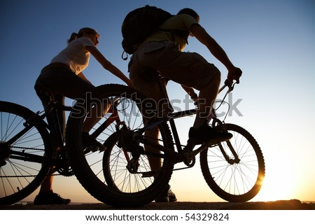 Beautiful Couple on bicycles on the brink of a rock and look afar from rock breakage - stock photo
