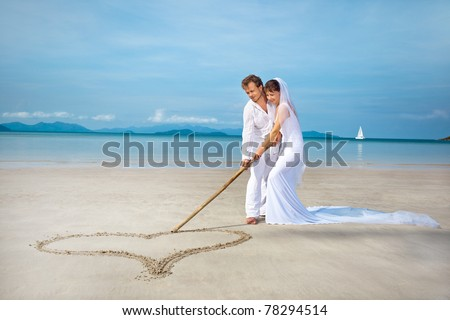 beautiful couple on the beach in wedding dress drawing heart - stock photo