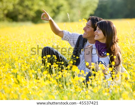 Beautiful couple outdoors pointing at something and smiling - stock photo