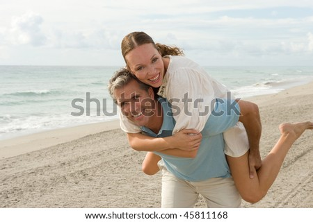 Beautiful couple playing at the beach