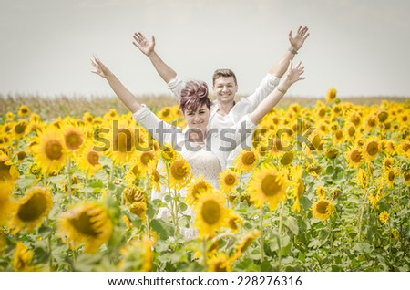 Beautiful couple raising arms in a sunflower field