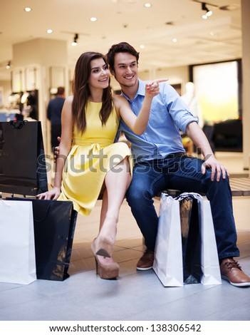 Beautiful couple resting after luxury shopping - stock photo