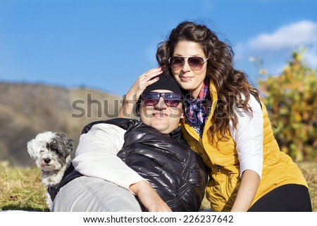 beautiful couple sitting and relaxing in the autumn mountain with their dog - stock photo