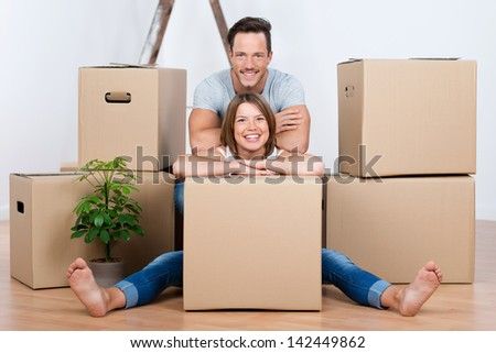 Beautiful couple sitting between many boxes in their new home - stock photo