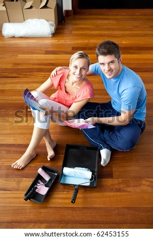 Beautiful couple sitting on the floor picking colors - stock photo