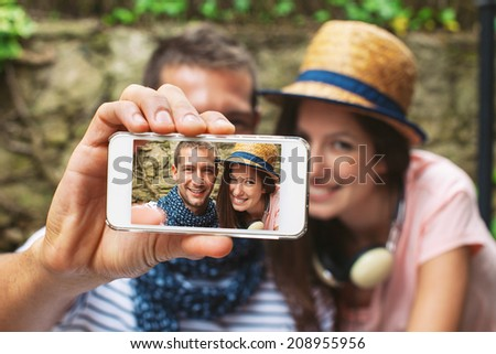 Beautiful couple smiling in your home garden./ Young couple taking selfie with smart phone camera in outdoors.  - stock photo