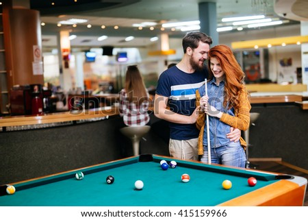Beautiful couple spending time together by playing pool - stock photo