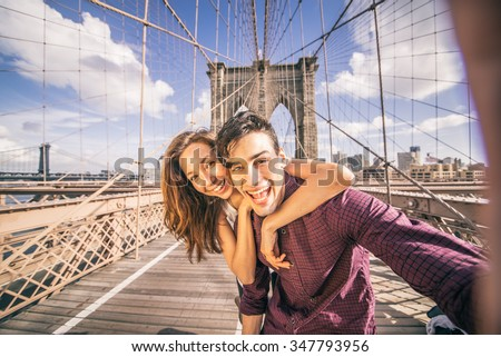 Beautiful couple taking selfie on Brooklyn Bridge, New York - Tourists having fun and photographing NY landmarks - stock photo