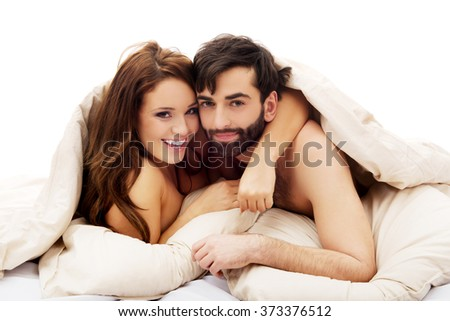Beautiful couple under the cover in their bed. - stock photo