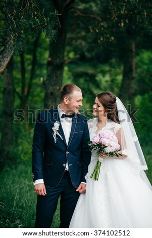 beautiful couple walking in the spring woods. beautiful bouquet