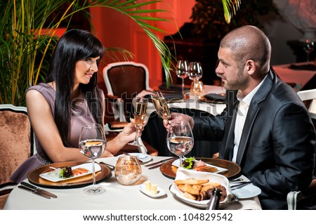 Beautiful couple with glasses of champagne at restaurant on romantic date - stock photo