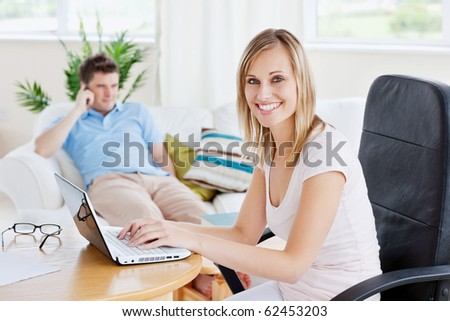 Beautiful couple with woman using laptop and man having a call sitting on a sofa in their living-room