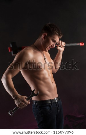 beautiful courageous man with a hammer and a wrench in jeans
