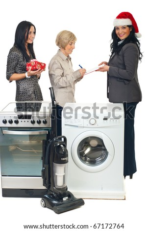 Beautiful courier woman with Santa hat making a special Christmas delivery with household appliances for a family mother and daughter - stock photo