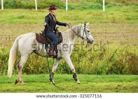 Beautiful cowgirl riding a white horse in a barrel race at a rodeo.