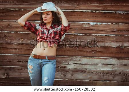 beautiful cowgirl style model posing on farmland near wood wall - stock photo