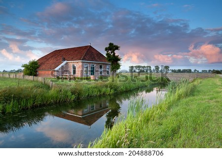 beautiful cozy farmland by river at sunset, Netherlands - stock photo