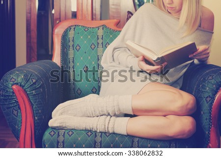 Beautiful cozy woman reading a book relaxing sitting in comfortable armchair. Christmas  holidays concept. - stock photo