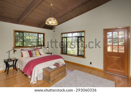 Beautiful Craftsman Bedroom with red cover and door outdoor leading to outdoor deck.  - stock photo