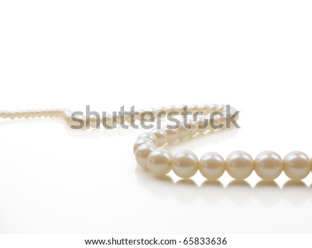Beautiful creamy pearl necklace on a white reflective surface - stock photo