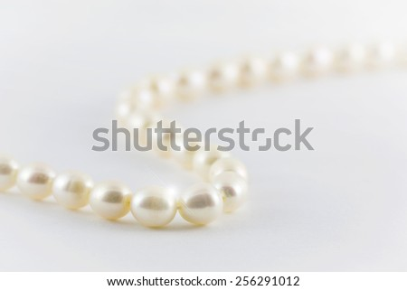Beautiful creamy pearls necklace isolated on white background. - stock photo