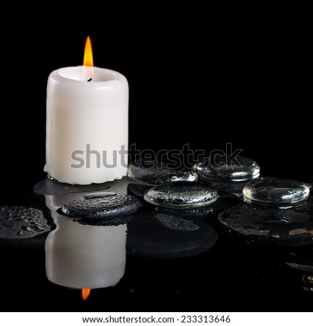 beautiful cryogenic spa concept of zen stones with drops, ice and candle on reflection water, closeup