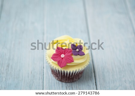 Beautiful cupcake with yellow frosting - stock photo