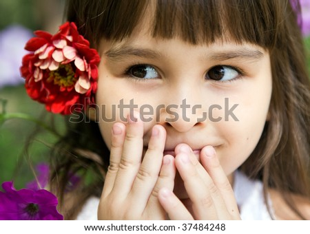 Beautiful curious girl with a flower in her hair in a summer garden