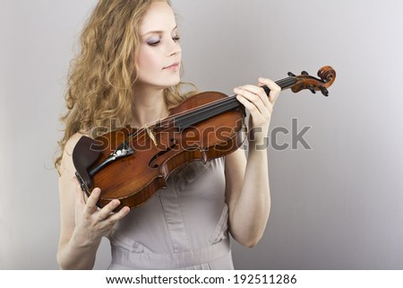 beautiful curly blonde in gray evening dress with red violin in her hands